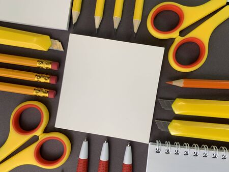Background texture: school stationery on the desk, yellow and orange. Stationery for the office, free space for writing. Concept: back to school, scissors and paper, office supplies. Zdjęcie Seryjne