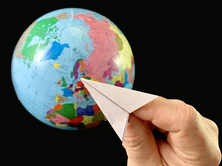 Paper plane in hand on a globe background, black background. Flight of the aircraft around the world. A man points his hand to the globe. Concept: travel, tourism, geography
