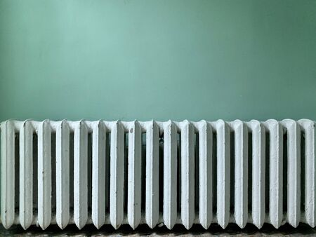 Cast iron batteries in a public building. Old heating radiators on the wall. Radiator sections for heating water in the room. Stock Photo