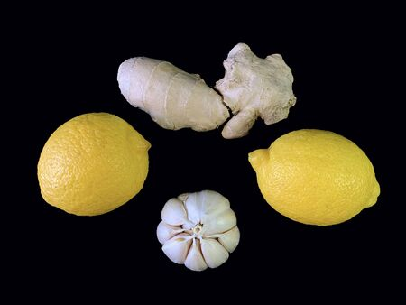 Garlic, ginger and lemon on a black background. Natural vitamins, antibiotics on a dark table. Concept: prevention of viral infections and corovirus at home.