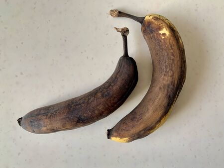 Spoiled, darkened bananas, on a white background. Old stale fruits on a light table. Perishable natural products, vitamins.