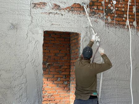 The craftsman puts the plaster on a brick wall. The builder is engaged in wall cladding. The painter - the plasterer works with a spray gun.