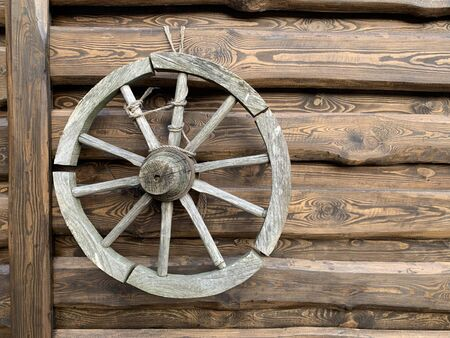 Wooden wheel from an old horse-drawn carriage. The wheel hangs on a wooden fence, as a decoration of the yard. Antique household items in the interior.