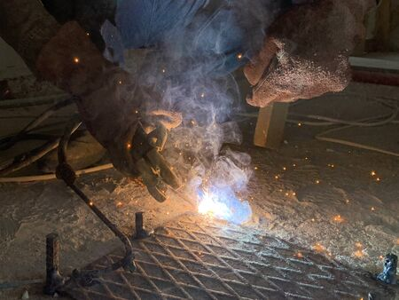Sparks from a welding torch during the work of the welder. The master solders a metal rod with a tool. The builder cuts reinforced steel. Archivio Fotografico