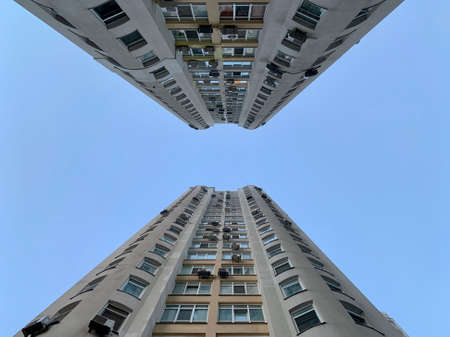 Multi-storey building against the blue sky. Tall new building with mirrored windows, bottom view. Background texture: high-rise, skyscraper, tower.