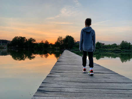 A boy walks along a wooden pier on the lake. A child is standing on a fishing platform. A young man walks across the bridge on the water. 免版税图像
