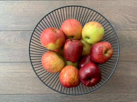 Ripe apples in a fruit bowl. Red, ripe apple in a metal vase. Delicious, juicy fruits on the plate.