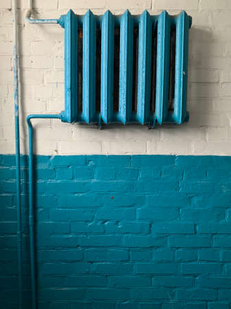 Cast iron batteries in a public building. Old heating radiators on the wall. Radiator sections for heating water in the room. Фото со стока