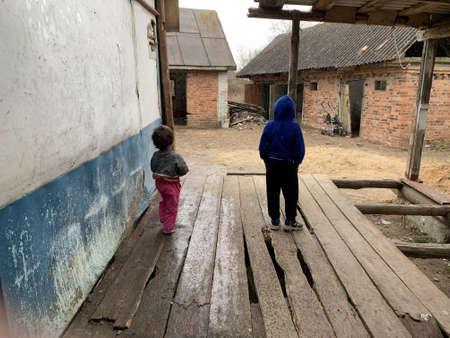 Poor children near the old house. Street children are hiding from the rain. Concept: poverty, orphans, raising children. Kiev region, Ivankovsky district, April 4, 2021