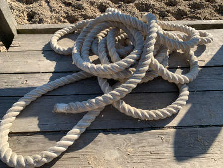 A thick rope lies on the wooden floor. Sturdy rope on a plank platform.