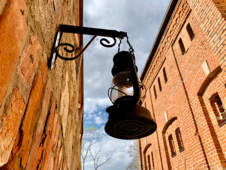 A lamp on the wall of an ancient castle. A kerosene lamp on a stone medieval building. An ancient lamp against the background of the wall and sky. Фото со стока