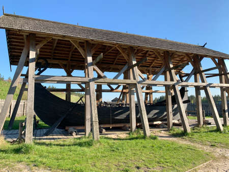 Wooden medieval boat under a canopy. An old wooden ship in the Kievan Rus park. Kiev region, Obukhiv district, Kopachevo village, May 10, 2021. Редакционное