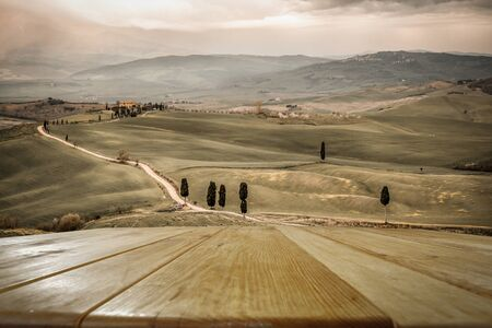 Autumn landscape of Tuscany and wooden board of free space for your decoration. Fall time and mood colors.