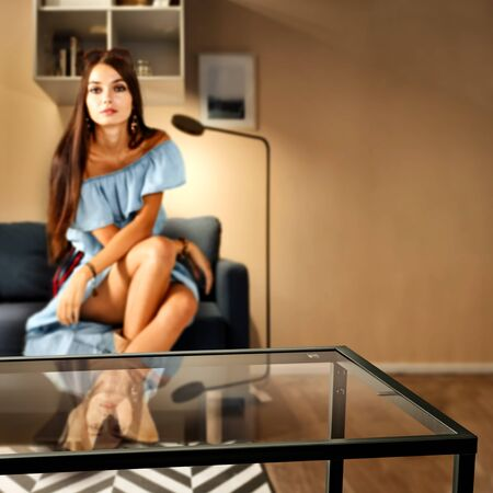 Glass table top with a blurred home interior background. A woman sitting on a sofa. Empty space background for your products and decoration. 스톡 콘텐츠