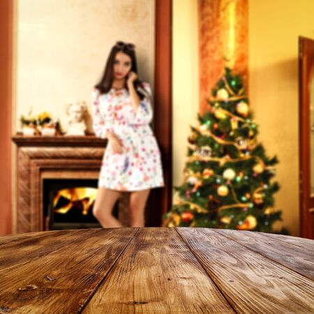Christmas tree and woman in nice comfortable cozy home interior. Table top background with empty space for products.