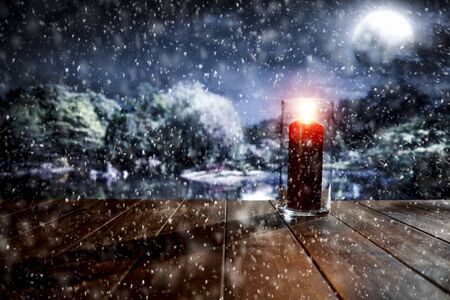 Snowy winter glimmering and shiny moonlight night landscape with wooden board top and lit lantern for products and decorations.