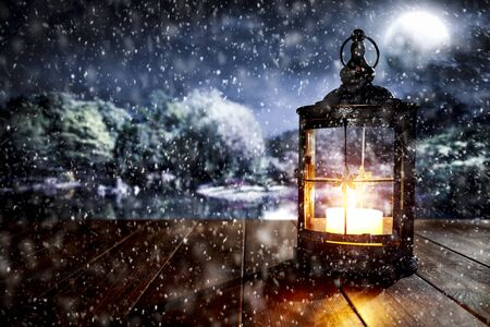 Snowy winter glimmering and shiny night landscape with wooden board top and lit lantern for products and decorations. Archivio Fotografico - 133353238