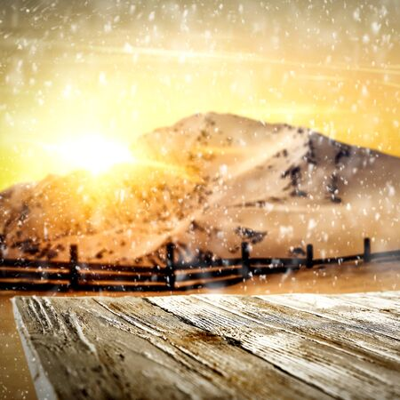 Snowy winter mountains background and snowy wooden table space for products and decorations or text. Archivio Fotografico - 133353241