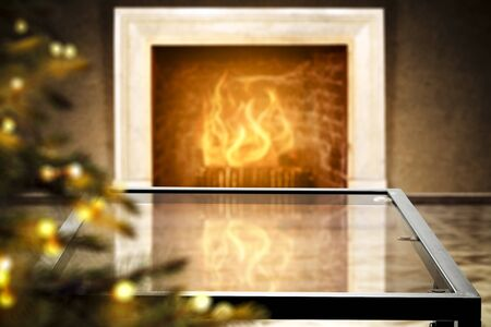 Glass table top with blurred fireplace in luxurious home interior. Table background with empty space for products and decorations.