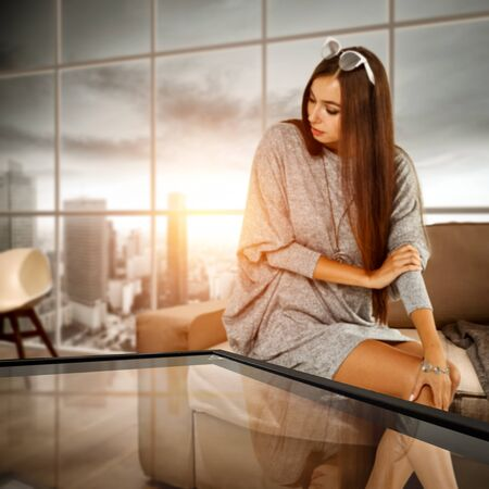 Glass table top with a blurred home interior background. A woman sitting on a sofa. Empty space background for your products and decoration. Urban view outside the window.