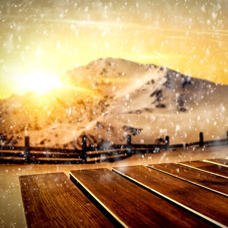Wooden table top with space for advertising products and decorations with blurred gold sunshine and mountains in snowy winter time. Archivio Fotografico - 133353197