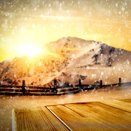 Snowy winter time with gold sunset and wooden table space for products and decorations or text. Archivio Fotografico - 133353204