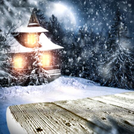 Wooden table top with snowy winter night landscape and a hut background. Archivio Fotografico - 133353171