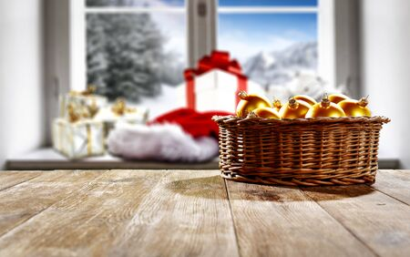 Blurred snowy winter sunshine landscape outside the kitchen window with christmas decorations and table top for products and decorations. Archivio Fotografico - 133353179