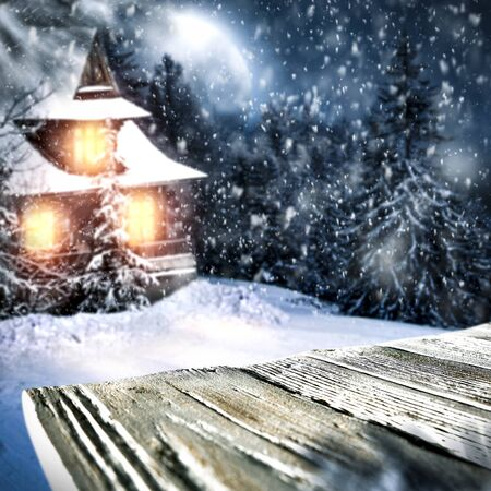 Snowy winter moonlight landscape with wooden board top for products and decorations. Archivio Fotografico - 133353186