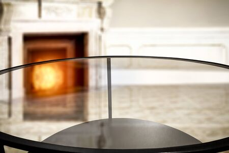 Glass table top with a blurred fireplace background. Empty space for your products and decoration. 스톡 콘텐츠
