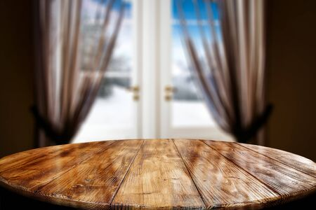 Wooden table top with a blurred window and curtains with home interior background. Empty space for your products and decoration. 스톡 콘텐츠