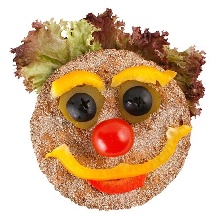 A smiling face composition made of food: bread, lettuce, pepper, tomato, olive. Isolated on a white background.