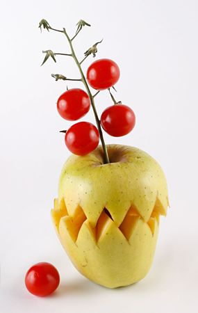A composition made of an apple and tomatoes. White background.