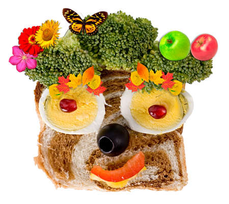 A happy face composition made of foodstuff: bread, egg, pepper, pomegranate, olive and broccoli. Isolated on a white background. Stock Photo