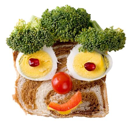 A smiling face composition made of foodstuff: bread, egg, pepper, pomegranate, tomato and broccoli. Isolated on a white background.