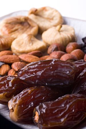 A composition of dried dates, figs, hazelnuts, almonds and prunes. Close-up. Stock Photo