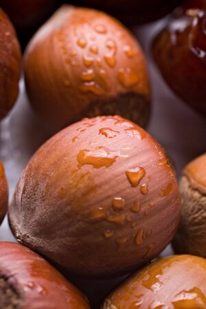 Hazelnuts and drops of water. Extreme close-up with shallow depth of focus.