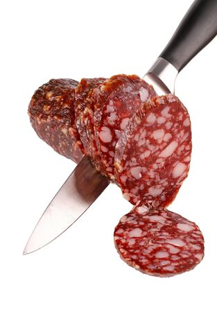 A smoked sausage sliced and a knife. Isolated on a white background. Stock Photo