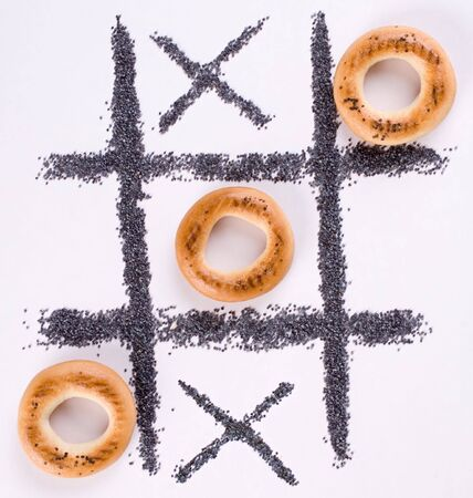 A tic-tac-toe game with bagels and poppy-seed. Stock Photo