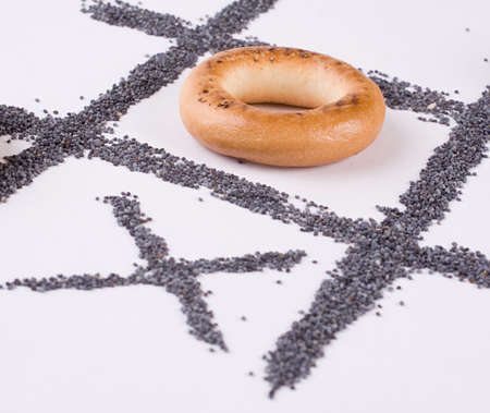 A tic-tac-toe game with bagels and poppy-seed. Close-up. Stock Photo