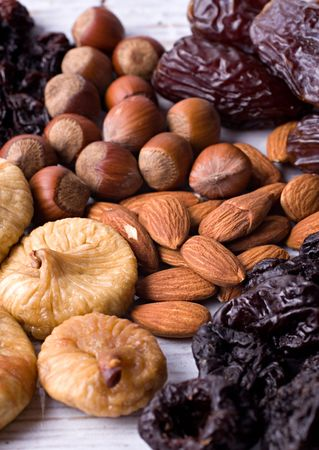 A composition of dried figs, prunes, hazelnuts, almonds and dates. Close-up.