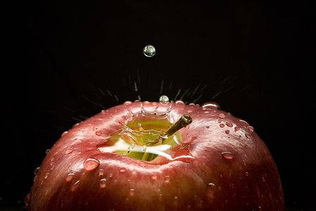 An apple, falling drops of water and a picturesque splash. Close-up.