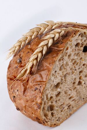 A loaf of bread sliced with a couple of wheat ears on it. The bread has a very distinct porous texture with lots of grains.
