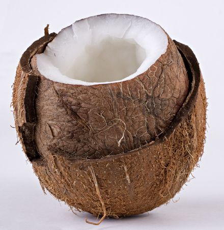 An open coconut isolated on a light gray background. Close-up. The shell is broken and the well-textured rape flesh can be seen.