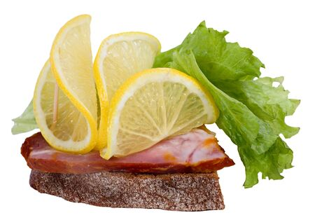 A sandwich with a slice of bacon, decorated with lemon and lettuce. Isolated on a white background.