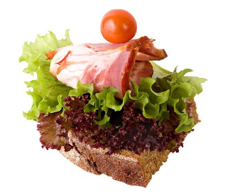 A sandwich with a slice of bacon, decorated with a tomato and leaves of green and red salad. Isolated on a white background.