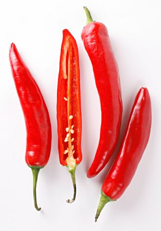 A composition of four chili peppers on a white background. One of the peppers is cut lengthwise showing seeds and internal texture.