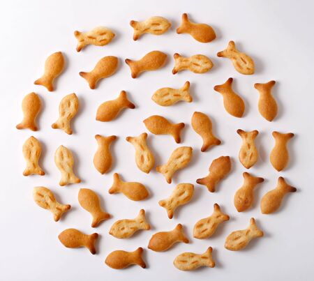 Small crackers in a form of fish are laid out in circles. A view from above. White background.