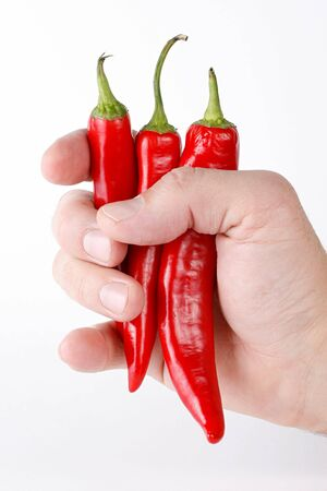 A mans hand holding three red chili peppers. White background. Stock Photo