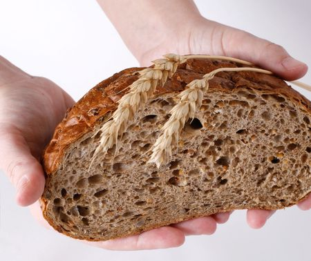 Womans hands offering a loaf of brown bread. There are two wheat-ears on the loaf. White background. Stock Photo